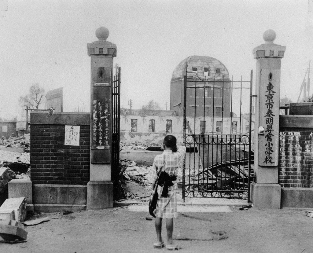 震災で崩壊した泰明尋常小学校の門前に佇む児童